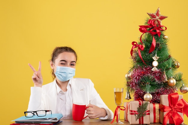 Front view female doctor sitting in protective mask on the yellow background with christmas tree and gift boxes