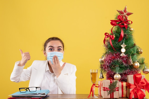 Front view female doctor sitting in protective mask on yellow background with christmas tree and gift boxes