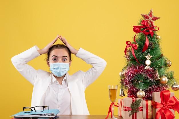 Medico femminile di vista frontale che si siede nella mascherina protettiva su priorità bassa gialla con l'albero di natale e confezioni regalo Foto Gratuite
