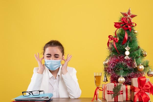 Medico femminile di vista frontale che si siede nella mascherina protettiva su priorità bassa gialla con l'albero di natale e confezioni regalo