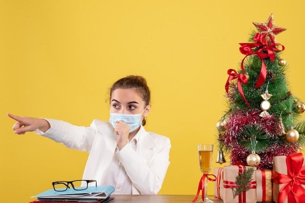 Front view female doctor sitting in protective mask on yellow desk with christmas tree and gift boxes