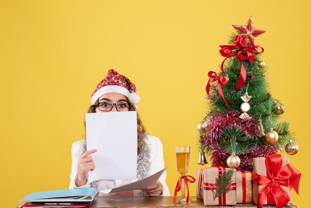 Medico femminile di vista frontale che si siede e che legge i documenti