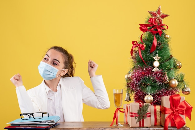 Front view female doctor sitting in sterile mask on the yellow background with christmas tree and gift boxes