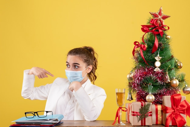 Front view female doctor sitting in sterile mask on yellow background with christmas tree and gift boxes