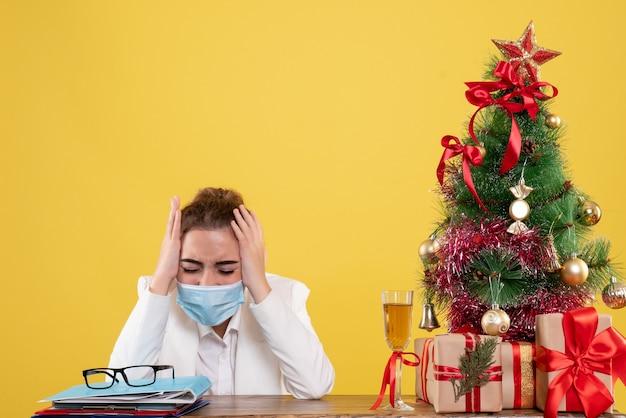 Medico femminile di vista frontale che si siede nella maschera sterile su fondo giallo con l'albero di natale e confezioni regalo
