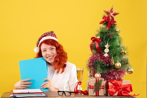 Medico femminile di vista frontale che si siede dietro la tavola e che tiene i documenti su fondo giallo con l'albero di natale e le confezioni regalo
