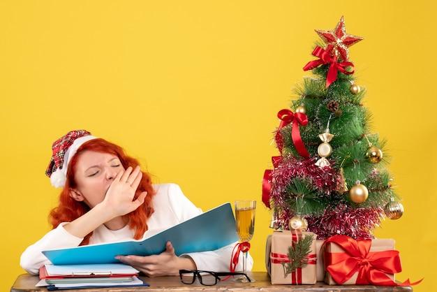 Medico femminile di vista frontale che si siede dietro la tabella che legge i documenti e che sbadiglia su fondo giallo con i contenitori di regalo e dell'albero di natale