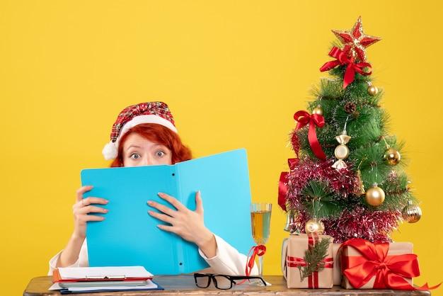 Medico femminile di vista frontale che si siede dietro il tavolo e la lettura di documenti su sfondo giallo con albero di natale e scatole regalo