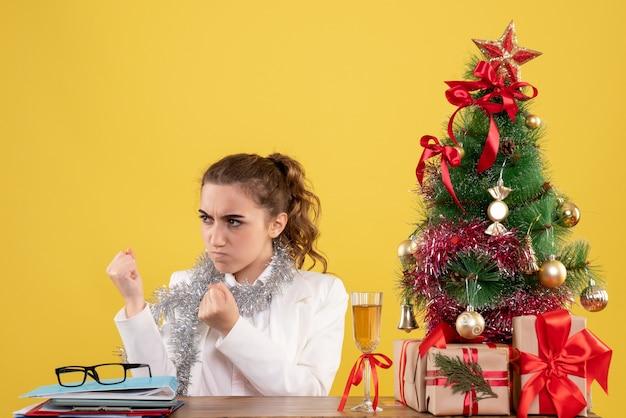 Medico femminile di vista frontale che si siede dietro il tavolo con la faccia arrabbiata su sfondo giallo con albero di natale e scatole regalo