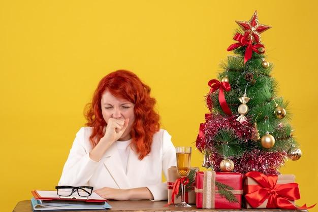 Medico femminile di vista frontale che si siede dietro la tavola con i regali di natale che sbadigliano su fondo giallo