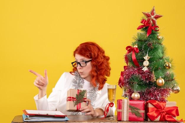 Medico femminile di vista frontale che si siede dietro il tavolo con i regali di natale su uno sfondo giallo con albero di natale e confezioni regalo