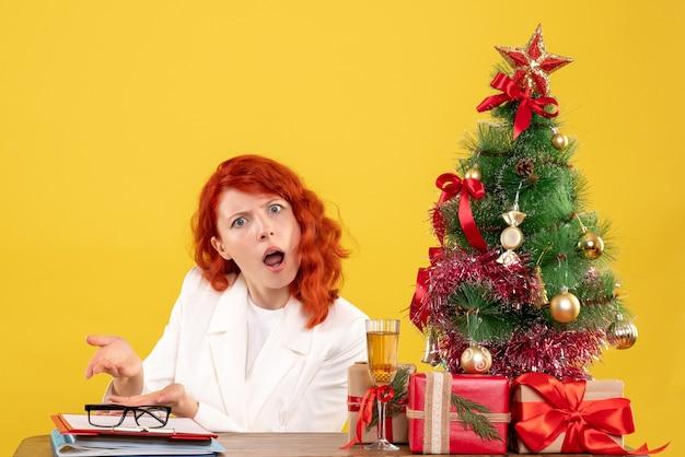Medico femminile di vista frontale che si siede dietro la tavola con i regali di natale su fondo giallo