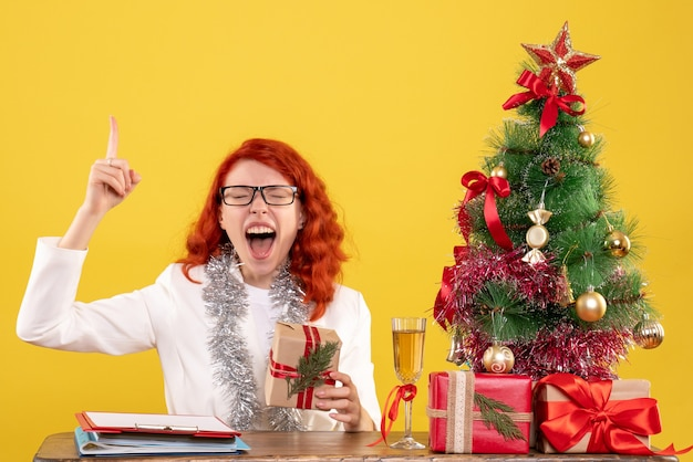 Medico femminile di vista frontale che si siede dietro la tavola con i regali di natale sullo scrittorio giallo