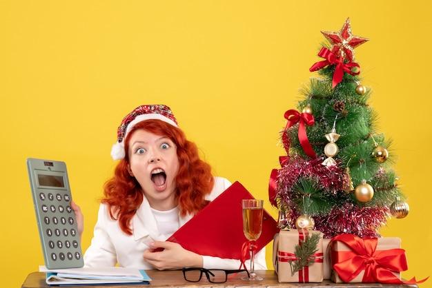 Medico femminile di vista frontale che si siede dietro la tavola con i regali che tengono il calcolatore su fondo giallo con l'albero di natale e le confezioni regalo