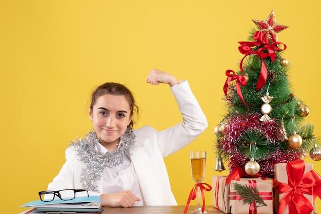 Medico femminile di vista frontale che si siede dietro il tavolo con regali di natale e albero che flette su sfondo giallo