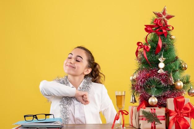 Medico femminile di vista frontale che si siede dietro la tavola con i regali di natale e l'albero su fondo giallo