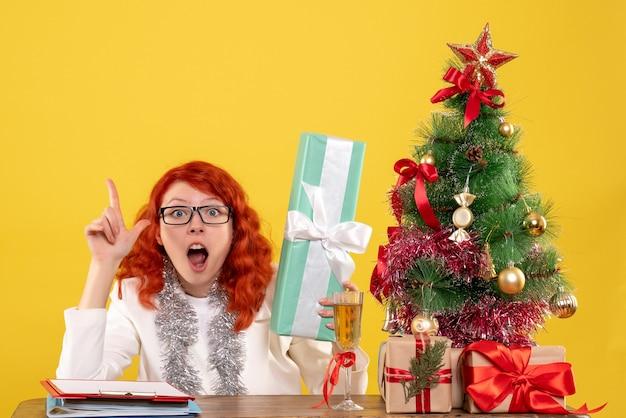 黄色の背景にクリスマスプレゼントと木と一緒に座っている正面図の女性医師