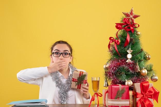 Вид спереди женщина-врач сидит с рождественскими подарками и елкой на желтом фоне h