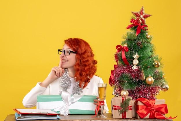 Вид спереди женщина-врач сидит с рождественскими подарками и елкой на желтом фоне