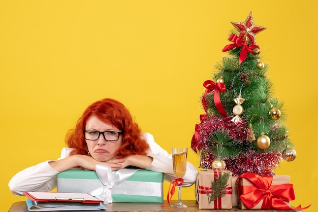 크리스마스 선물 및 노란색 배경에 나무에 앉아 전면보기 여성 의사
