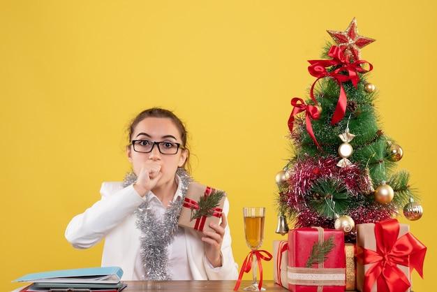 Вид спереди женщина-врач сидит с рождественскими подарками и елкой на желтом столе