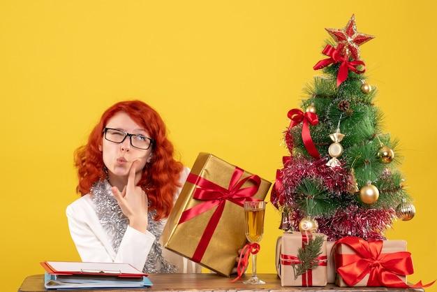 黄色の背景にクリスマスプレゼントと座っている正面図の女性医師