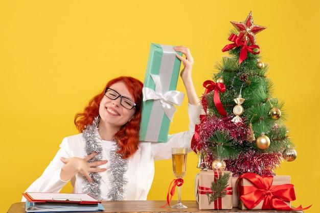 크리스마스와 함께 앉아 전면보기 여성 의사 노란색 배경에 선물