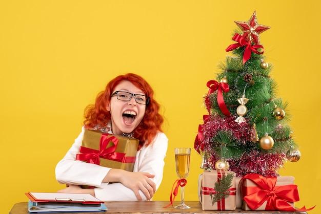 Вид спереди женщина-врач сидит с рождественскими подарками на желтом фоне
