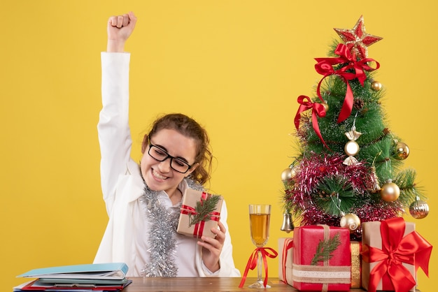 Front view female doctor sitting with christmas presents and tree rejoicing on yellow background