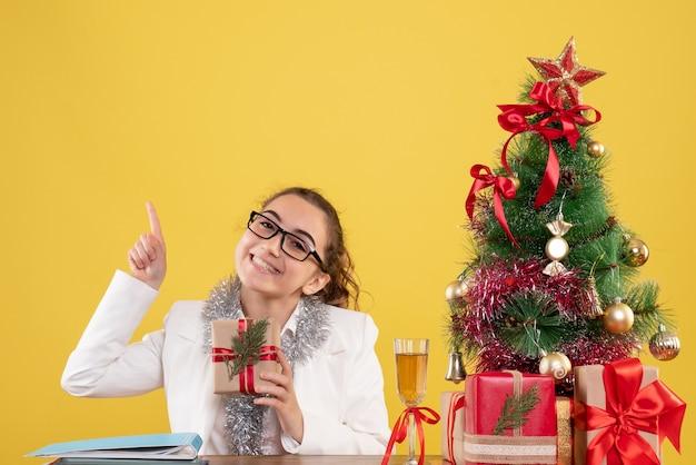 Medico femminile di vista frontale che si siede con i regali di natale e l'albero su fondo giallo