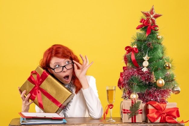 Front view female doctor sitting with christmas presents and tree on yellow background