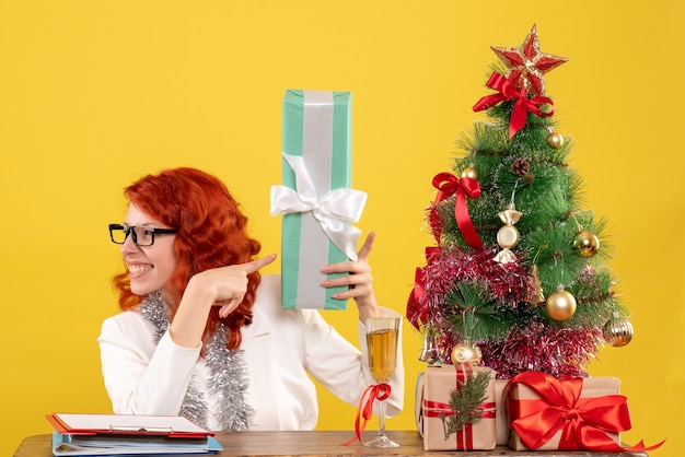 Front view female doctor sitting with christmas presents and tree on the yellow desk