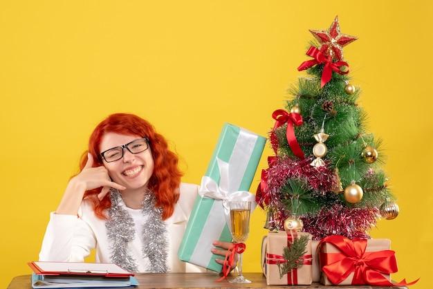 Medico femminile di vista frontale che si siede con i regali di natale e l'albero sullo scrittorio giallo