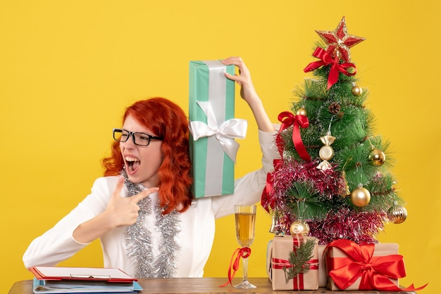 Front view female doctor sitting with christmas presents and tree on yellow desk