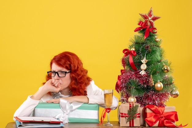 Medico femminile di vista frontale che si siede con i regali di natale e l'albero sul giallo