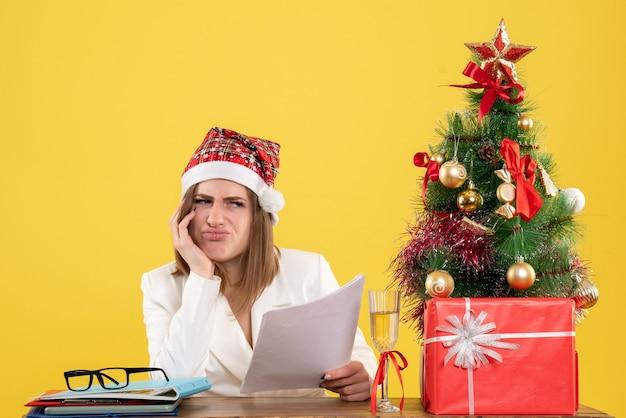Medico femminile di vista frontale che si siede con i regali di natale che tengono i documenti annoiati su fondo giallo