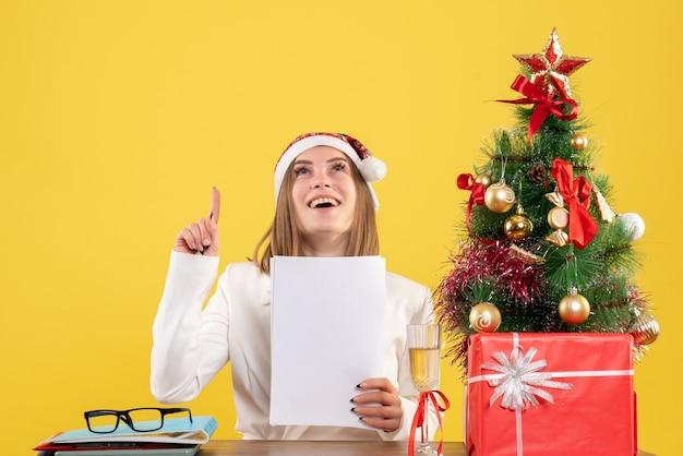 크리스마스와 함께 앉아 전면보기 여성 의사는 노란색 배경에 문서를 들고 선물
