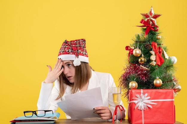 クリスマスと一緒に座っている正面図の女性医師は黄色の背景にドキュメントを保持している