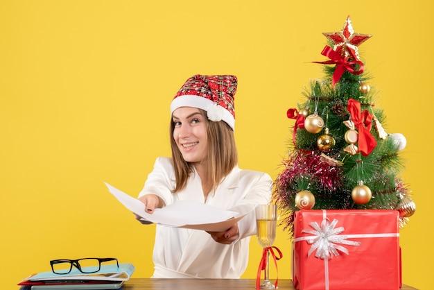 Вид спереди женщина-врач, сидящая с рождественскими подарками, держит документы на желтом фоне