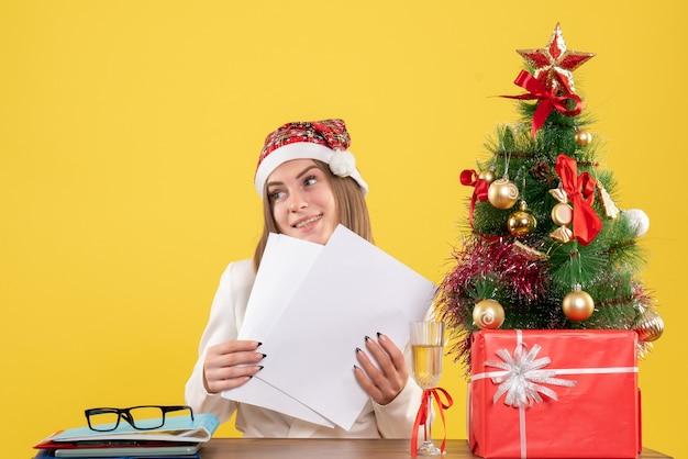 Medico femminile di vista frontale che si siede con i regali di natale che tengono i documenti su fondo giallo