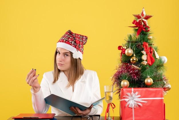 クリスマスプレゼントと黄色のファイルを保持している正面図