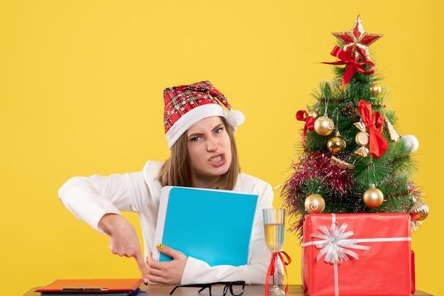 Medico femminile di vista frontale che si siede con i regali di natale che tengono i file su fondo giallo