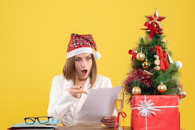 クリスマスと一緒に座っている正面図の女性医師は、黄色の背景にドキュメントを読んで提示します