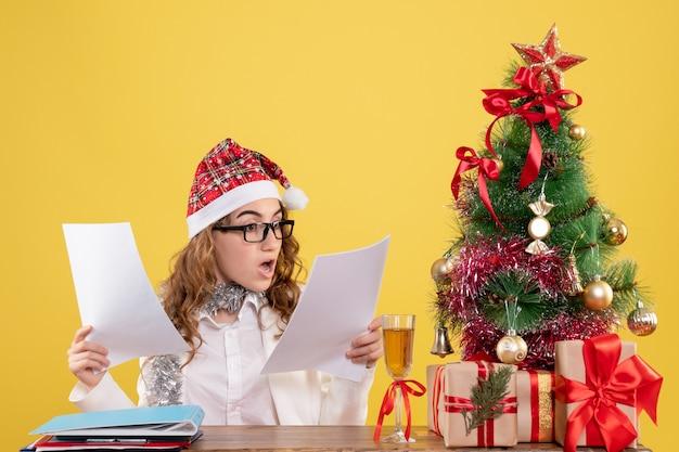크리스마스와 함께 앉아 전면보기 여성 의사는 나무와 노란색 배경에 문서를 들고 선물