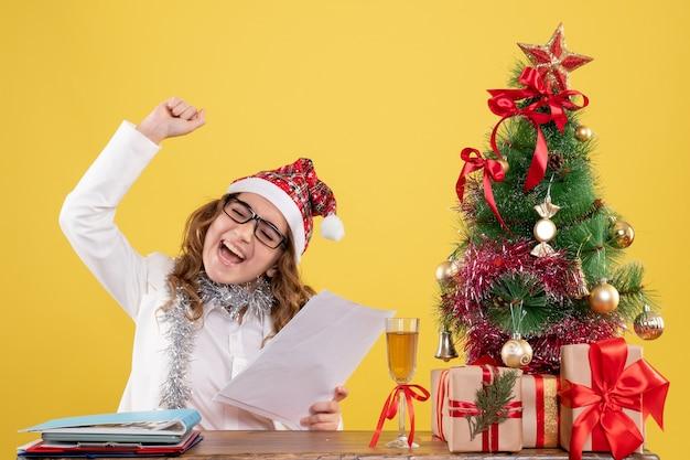 Medico femminile di vista frontale che si siede con l'albero dei regali di natale e che tiene i documenti su fondo giallo con i contenitori di regalo e dell'albero di natale