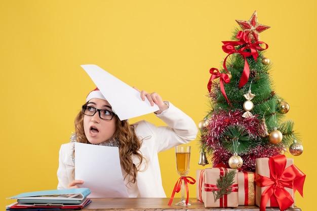 Medico femminile di vista frontale che si siede con l'albero dei regali di natale e che tiene i documenti su fondo giallo