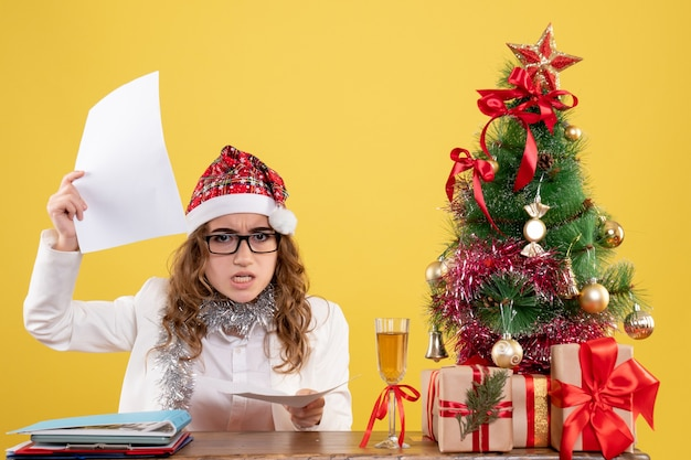 Front view female doctor sitting with xmas presents tree and holding documents on yellow background