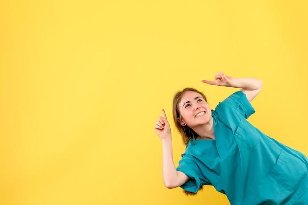 黄色の背景に笑みを浮かべて正面図女性医師薬感情ウイルス病院の健康