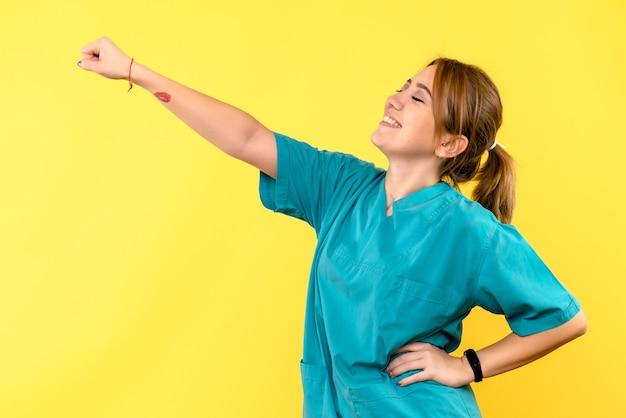 Medico femminile di vista frontale che sorride sullo spazio giallo
