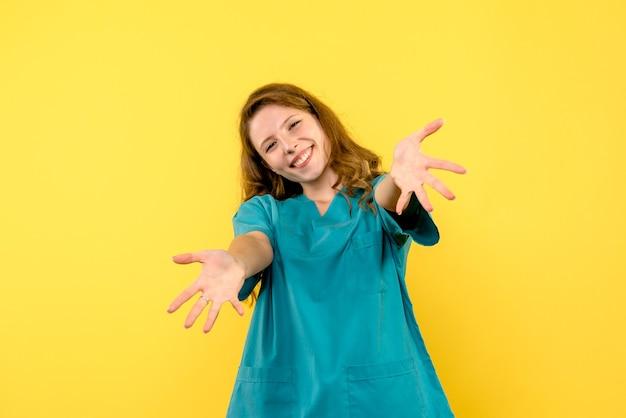 Vista frontale della dottoressa sorridente sulla parete gialla